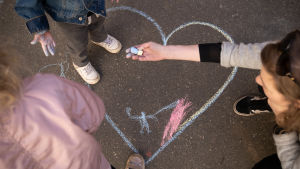 Äiti ja pienet lapset piirtävät katuliiduilla sydäntä asfalttiin.