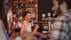 Ensam kvinna dricker vin i baren och tittar på ett par i bordet bredvid.