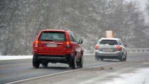 Två bilar kör på en väg som är slaskig. Diket är vitt av snö.