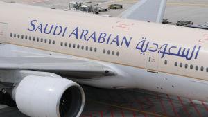 Ett Saudi Arabian Airlines-flygplan står parkerat på ett flygfält.