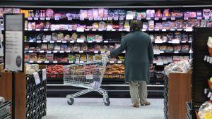Kvinna i matbutik står bredvid en kundvagn.
