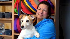 En kvinna står med en liten, ljus hund i famnen, i bakgrunden syns rullar med remmar i olika färger.