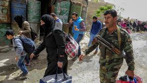 Civila började lämna Douma på söndag förmiddag med hjälp av den syriska armén