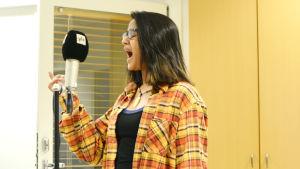 En bild på en kvinna som sjunger i en studio.