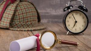 en hopvikt pappersrulle, ett förstoringsglas, en väckarklocka och en rutig filthatt som är typisk för detektiv Sherlock Holmes.
