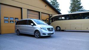 En stor silverfärgad bil står bredvid en gul buss utanför ett garage.