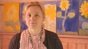 Personporträtt av Monica Boström. I bakgrunden syns teckningar.