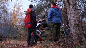 Två ungdomar står och pratar bredvid en vespa i höstväder.