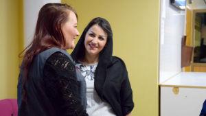 Två kvinna står och pratar med varandra, den ena kvinnan har en huvudduk.