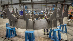 En person granskar en stor rund stålkonstruktion för ubåtar inne i en stor varvshall.
