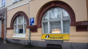 Utsidan av ett stenhus med två valvliknande fönster. I fönstren skyltar som visar att Västra Nylands redaktion och Hangötidningens redaktion finns inne i byggnaden.