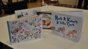 Flera barnböcker står på rad på ett bord.