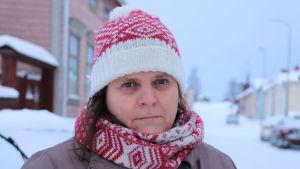 En kvinna med rödvit mössa och halsduk står på en snöklädd gata.