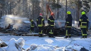 Brandmän håller på med eftersläckning vid en brand.
