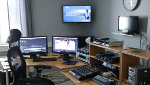 Ett rum fyllt med datorskärmar och elektronisk utrustning.