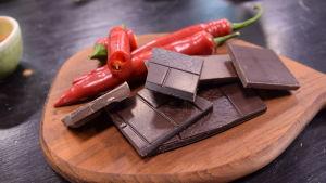 Chiliä ja suklaata leikkuulaudalla keittiössä