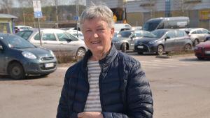 Kvinna står på en parkering och ler