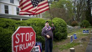 """Demonstrant med amerikansk flagga och """"Stop Trump""""-trafikskylt"""