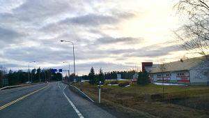 En väg fotograferat ur en bils vindruta. Till höger en byggnad och i horisonten träd.