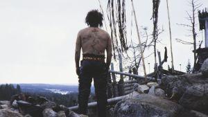 Näyttelijä Esko Salminen Pohjolan isännän roolissa Rauta-aika tv-sarjassa. Pohjolan isäntä seisoo selin kalliolla, hänen paljaaseen selkäänsä on piirretty kartta.