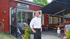 En manlig kock utanför en restaurangterass.