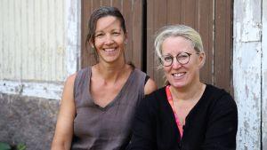 Två kvinnor ler framför kameran.