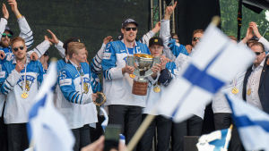 Anttila och Lejonen står på scenen i Kajsanemiparken och firar guldet