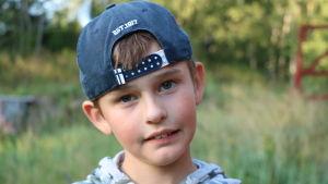 En pojke med bakåtvänd keps och munkjacka.