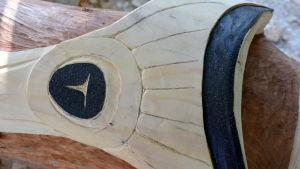 Närbild av laxfigur på en totempåle.