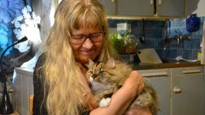 Ann-Sophie sitter i köket med en katt i famnen.