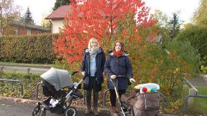 Johanna Lehmuskoski (vänster) och Erika Louhivuori står framför ett höstigt, orangebladigt träd och håller i sina barnvagnar.