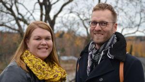 En man och en kvinna tittar in i kameran och ler.