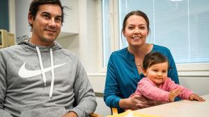 En mamma, pappa och barn vid ett bord.