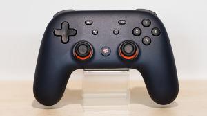 En svart spelkontroll med knappar i orange.