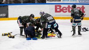 Patrik Puistola ligger på isen omringad av lagkamrater.