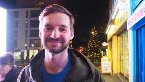 Jack står på en gata framför en julgran och tittar in i kameran.