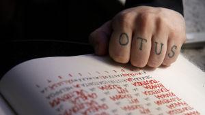Susinukke Kosolan käsi nyrkissä kirjan päällä. Rystysiin tatuoitu OTUS.