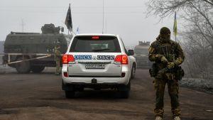 Ett OSSE-märkt fordon passerar en ukrainsk soldat på väg mot gränsposteringen Majorsk. OSSE övervakade fångutväxlingen.