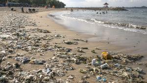 En strand i Bali som är översvämmad av plast