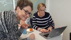 Kirsi Mikkola undervisar hur Tripadvisor fungerar för Minna Ermala.