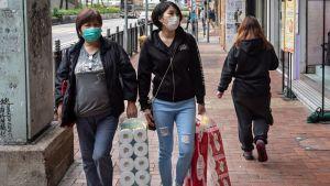 Två personer i munskydd går på gatan och håller i toalettpapper.