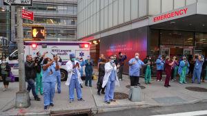 Läkare och sjukskötare vid Langone sjukhuset i New York tar emot hyllningar av folk ute på gatorna. Över 10 000 insjuknade har dött i New York City.