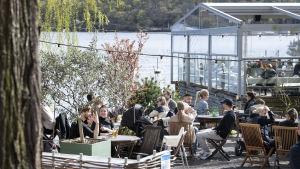 Människor på utomhusrestaurang i Stockholm med växthus och hav i bakgrunden.
