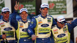 Marcus Grönholm och Timo Rautiainen firar efter sitt sista VM-rally tillsammans med vinnarna Mikko Hirvonen och Jarmo Lehtinen.