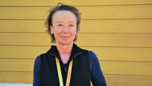 Laura Hollsten, en brunhårig kvinna som är klädd i en blå tröja och en svart väst står framför en gul vägg