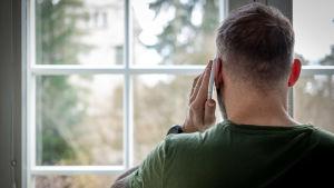 En man pratar i telefon samtidigt som han tittar ut genom ett fönster.