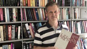 USA-intresserade statsvetaren Lauri Rapeli håller i årsboken från skolan han gick i under utbytesåret i USA i mitten av 1990-talet.