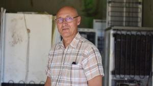 En skallig man som står framför gamla tvättmaskiner.
