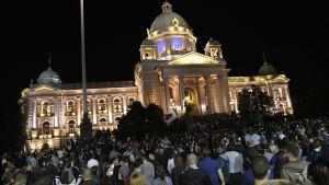 Folkmassa utanför upplyst parlamentsbyggnad i Belgrad.