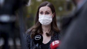 Sanna Marin utanför Ständerhuset 15.10.2020. Hon bär munskydd och intervjuas av journalister.